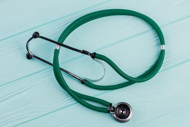 Groene stethoscoop op turkooizen achtergrond. houten gestructureerd bureau.
