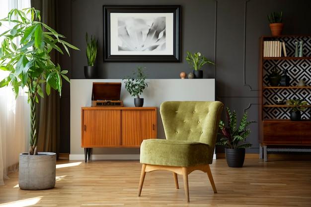 Groene stoel naast plant in grijs woonkamer interieur met poster boven houten kast. echte foto