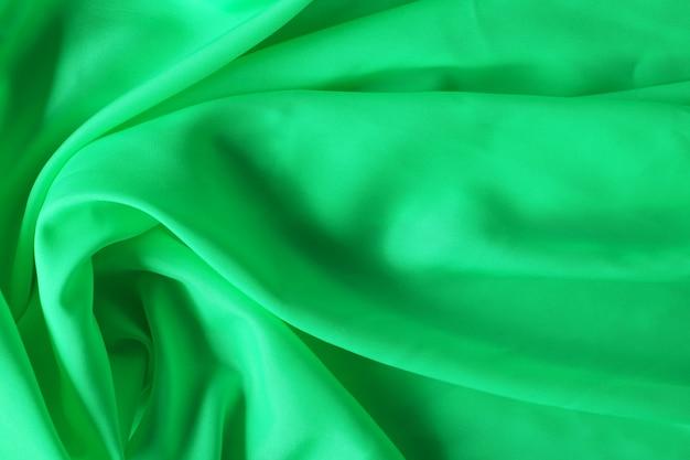 Groene stof textuur achtergrond, verfrommeld stof achtergrond met zachte golven
