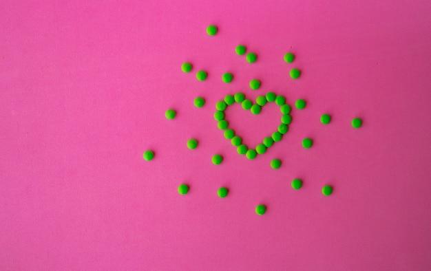 Groene tabletten en hartvormige tabletten, hart gevoerde tabletten voor cardiologie hartziekte, prebiotica en probiotica supplementen voor darmgezondheid, apotheek en ziekenhuisconcept