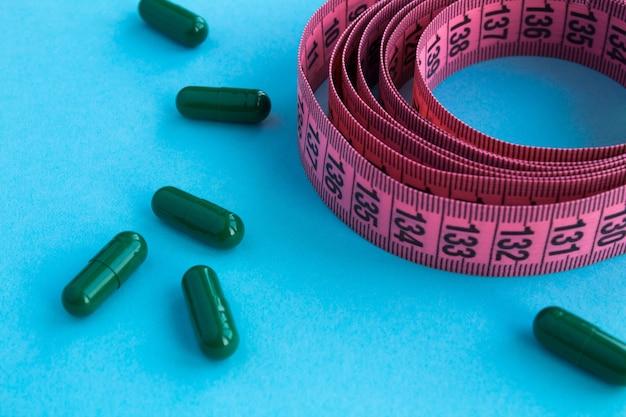 Groene tabletten en roze centimeter op de blauwe achtergrond