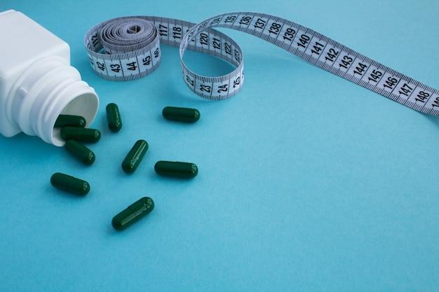 Groene tabletten en witte centimeter op het blauw