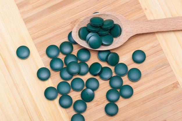 Groene tabletten - spirulina of chlorella in een houten lepel. gezond woonconcept.