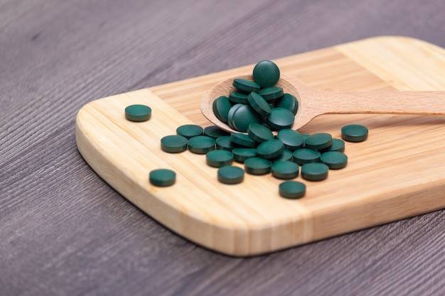 Groene tabletten - spirulina of chlorella in een houten lepel.