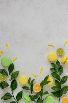 Groene takken met gele bloemblaadjes, geassorteerde macarons, schijfjes citroen, limoenwit betonnen oppervlak