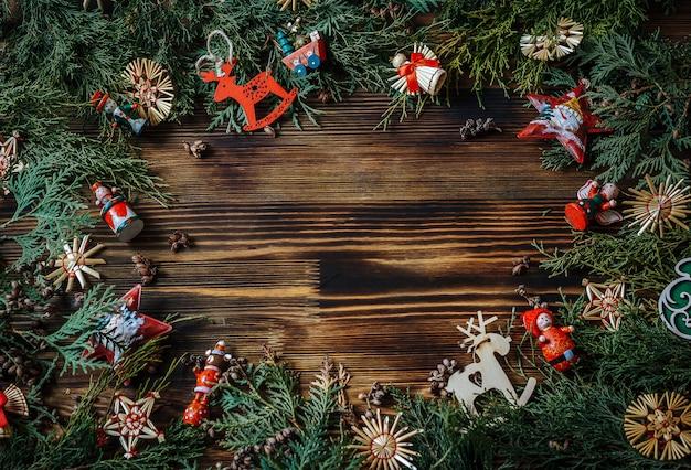 Groene takken van een kerstboom met kerstmisspeelgoed op het oude hout