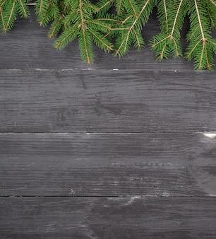 Groene takken van een kerstboom op een zwarte houten achtergrond