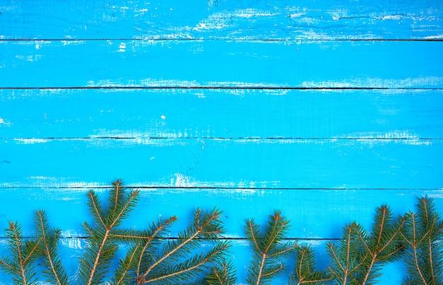 Groene takken van naalden op een blauwe achtergrond van armoedige planken