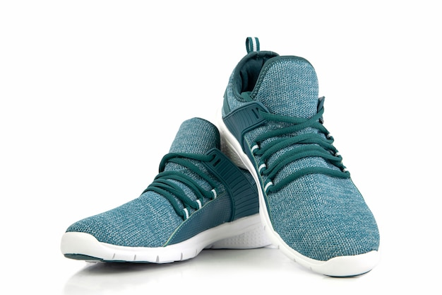 Groene tennisschoenen of sportloopschoen die op een witte achtergrond wordt geïsoleerd