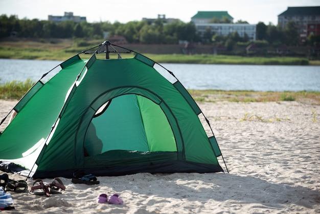 Groene tent op rivieroever tegen de achtergrond van de stad. camping. vrije tijd.