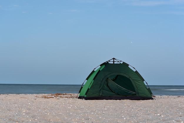 Groene tent op zandstrand tegen de zee en de blauwe hemelachtergrond. camping, actief toerisme.