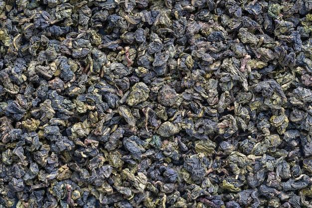 Groene thee bladeren achtergrond. oolong thee. abstracte voedsel texturen. close-up, bovenaanzicht. de high-end thee van china.