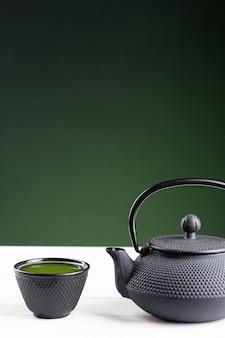 Groene thee en theepot op groene achtergrond op witte houten basis met copyspace. traditionele japanse drank. verticaal formaat.