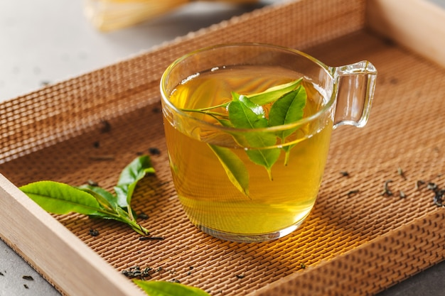 Groene thee gebrouwen in cup met theebladeren op tafel. detailopname.
