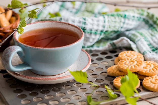 Groene thee in beker. een kopje thee met een rond koekje op een groen linnen geruit servet