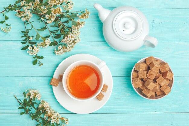 Groene thee in een keramische beker met takken van bloeiende boomtakken