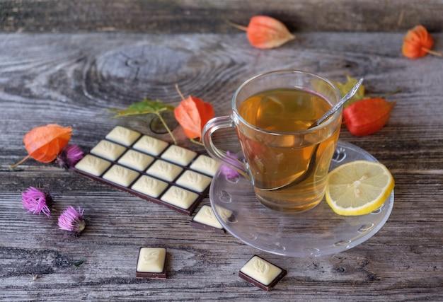 Groene thee in glas beker en chocolade op houten planken met herfstkleuren