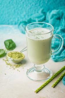 Groene thee matcha latte in een glazen beker op blauwe achtergrond concept van een gezonde voeding superfood antioxidant reiniging