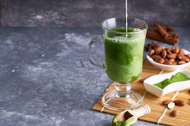 Groene thee matcha met room in glas op grijze stenen tafel
