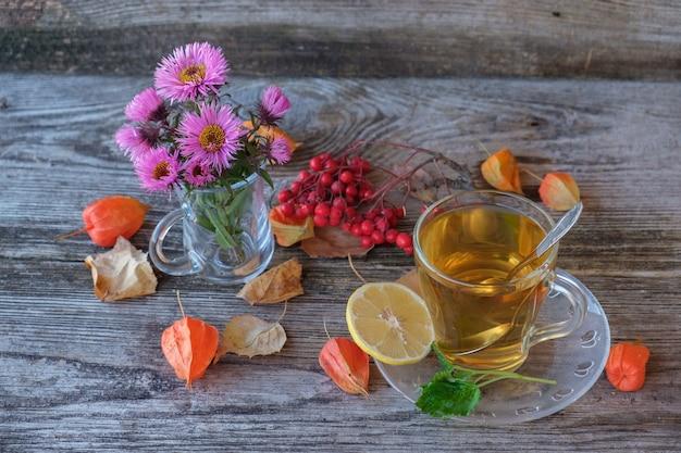 Groene thee met citroen en munt in een glazen mok op oude houten bord met herfstkleuren