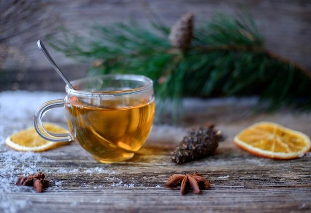 Groene thee met een glazen beker op een houten tafel met dennentakken, gedroogde sinaasappels, dennenappels, anijssterren en sneeuw