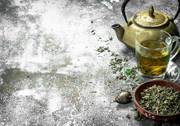 Groene thee met een theepot op rustieke tafel.