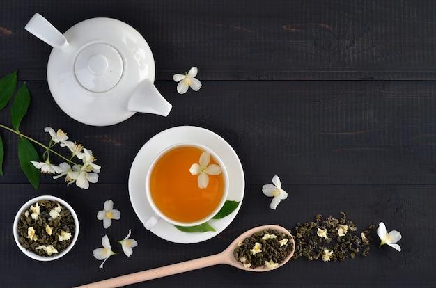 Groene thee met jasmijn in beker en theepot op donkere houten achtergrond met kopieerruimte. bovenaanzicht.