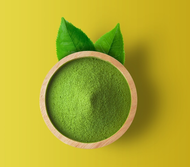Groene thee poeder in een kom en theeblaadjes geïsoleerd op gele achtergrond