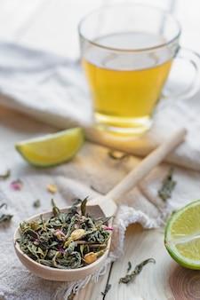 Groene theeblaadjes in een houten lepel op linnen textiel met limoen plakjes en mok gebrouwen thee, close-up