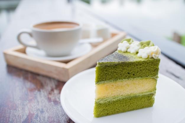 Groene theecake met koffieontbijt dat in openluchtrestaurant wordt geplaatst