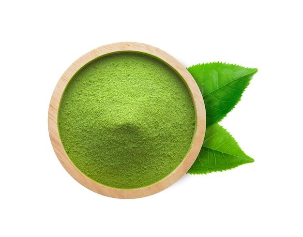 Groene theepoeder in een kom en theeblaadjes op witte muur