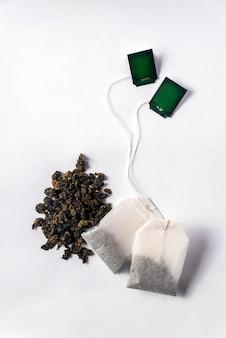 Groene theezakjes en losse groene thee op een witte achtergrond
