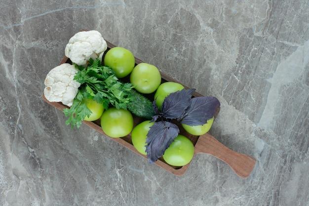 Groene tomaten en bloemkoolstukjes gegarneerd met amarant en peterselieblaadjes op een dienblad op marmer.