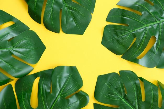 Groene tropische palmbladeren op heldere gele achtergrond.