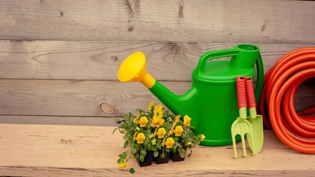 Groene tuingereedschap en bloemen staan op houten achtergrond