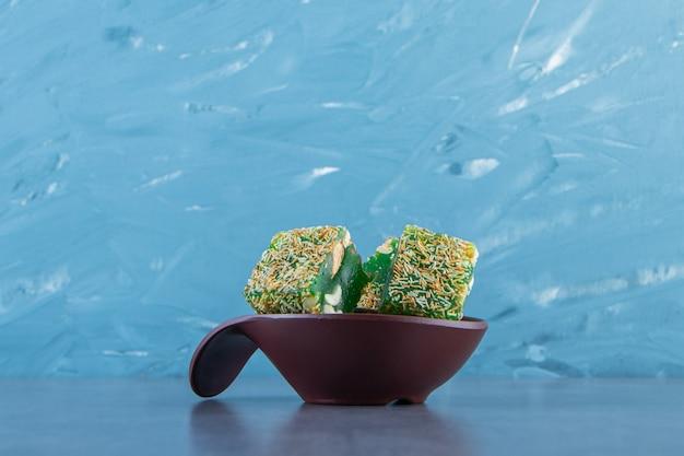 Groene turkse lekkernijen in een kom, op de marmeren achtergrond.