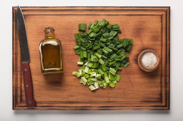 Groene uien en olijfolie op keukenbord