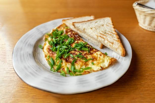 Groene uiomelet met broodtoosts op plaat. heerlijk, gemakkelijk en populair ontbijt
