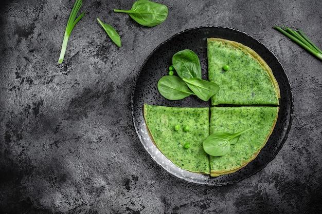 Groene vegan pannenkoeken met spinazie op zwarte plaat, donkere achtergrond, gezond ontbijt, vegetarisch eten, bovenaanzicht.