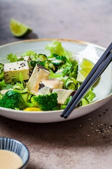 Groene vegan salade met broccoli, gerookte tofu en tahin dressing in een witte kom,