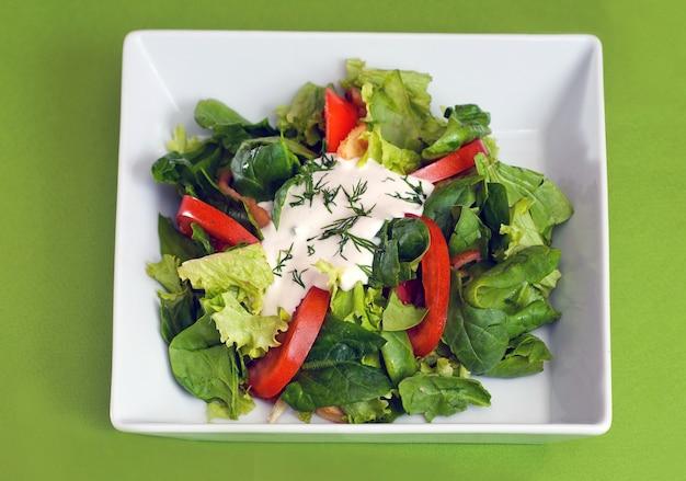 Groene vegan zomersla met spinazie, tomaten en zure room. gezond voedselconcept.