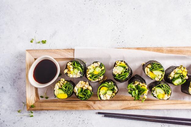 Groene veganist sushi rolt op een houten bord.
