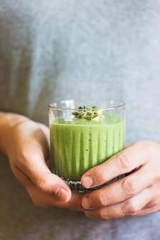 Groene veganistische smoothie met spinazie, banaan en gekiemde zaden in glas in mannelijke handen