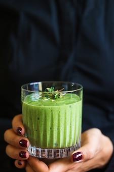Groene veganistische smoothie met spinazie, banaan en gekiemde zaden in glas in vrouwelijke handen op zwarte achtergrond schoon eten detox concept