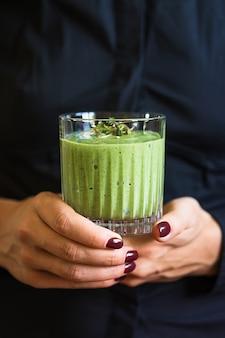 Groene veganistische smoothie met spinazie en gekiemde zaden in glas in vrouwelijke handen op zwarte ondergrond.