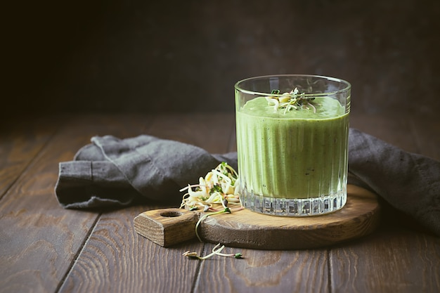 Groene veganistische smoothie met spinazie en gekiemde zaden op donkere houten ondergrond.
