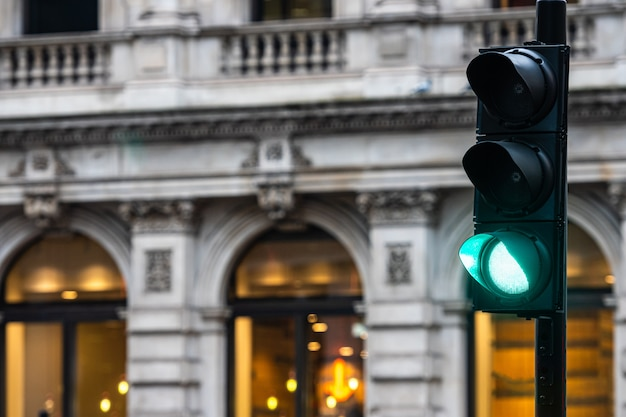Groene verkeerslichten voor auto's op vage gebouwen