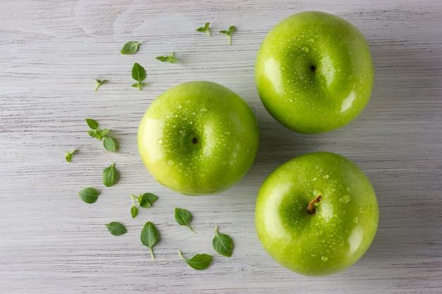 Groene verse appels en sommige basilicumbladeren op houten lijst