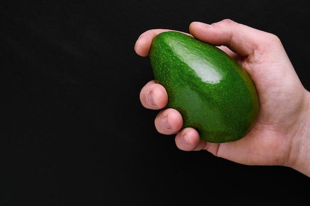 Groene verse avocado in mannelijke hand over zwarte achtergrond close-up