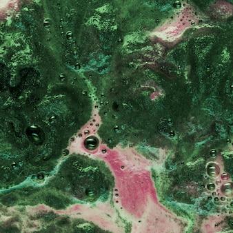 Groene vloeistof met roze schuim